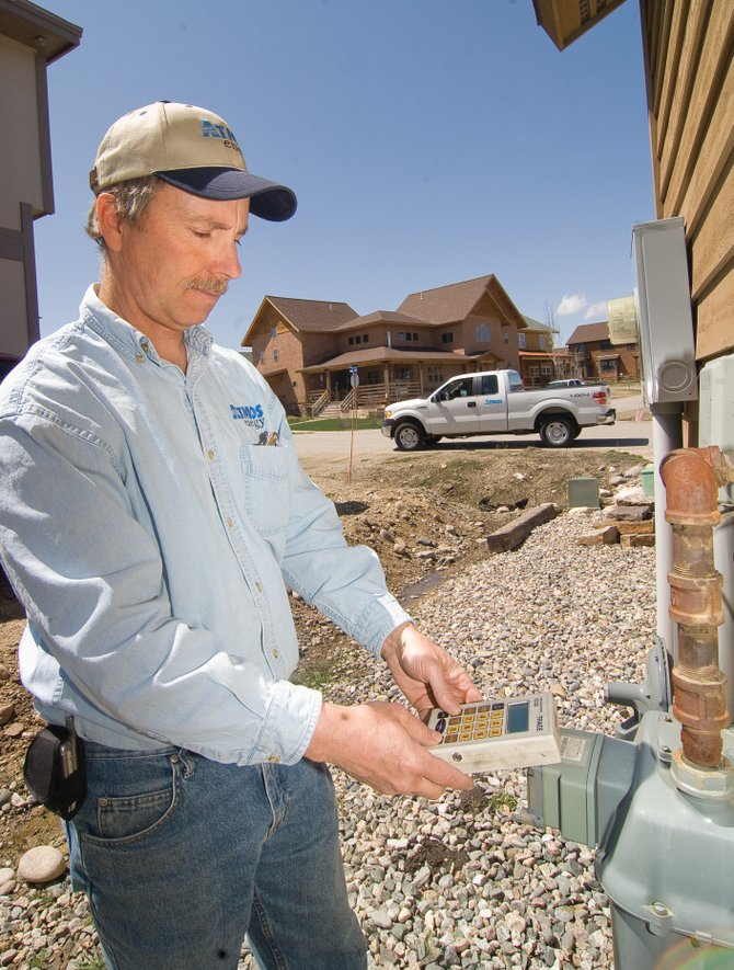 Atmos Energy's Mickey Walsh checks a gas meter at a home in West End Village. An energy efficiency program being offered by the utility provides discounted home energy audits, appliance rebates and other ways to help customers reduce their natural gas consumption.