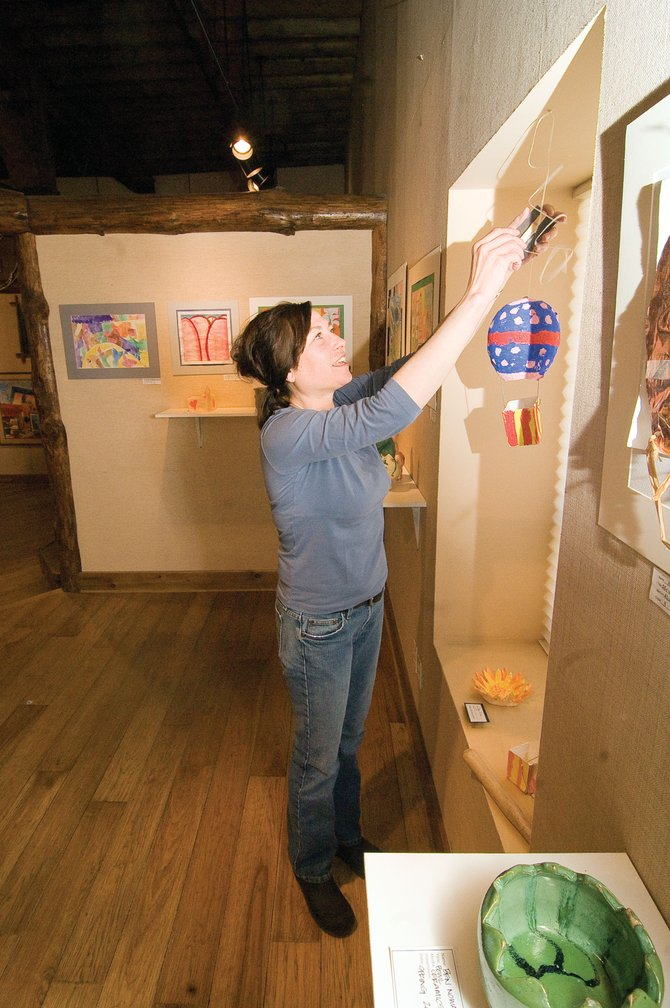 Gabrielle Savage hangs a piece of youth art at the Steamboat Springs Center for Visual Arts on Wednesday morning. The gallery features work by Steamboat Springs students at a First Friday Artwalk reception from 5 to 8 p.m. today.