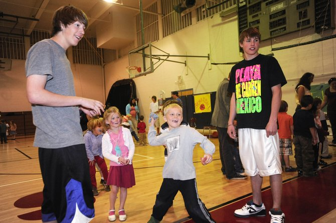 Steamboat Springs High School juniors Ty Hvambsal, left, and Shane Berube, right, watche Strawberry Park Elementary School kindergartner Ryan McNamara throw a bean bag during the Kids' Carnival on Wednesday morning at the high school. Senior Haley O'Brien led the organization of the annual event with help from classmates in the leadership class.