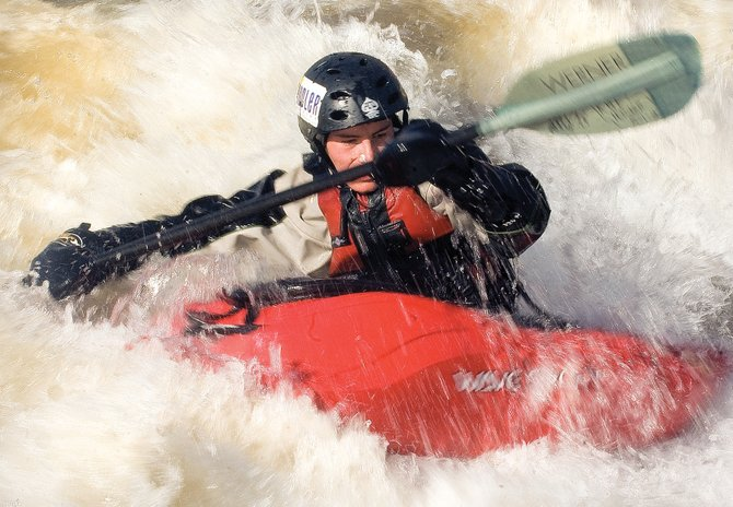 Kayaker Kyle Hornor plays in the fast-moving waters of the Yampa River on Wednesday evening. The spring melt has brought the river levels up in the past few weeks and also increased the possibility of flooding.
