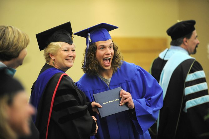 "CMC graduate Nate Wilson poses for a picture while receiving his diploma from Deborah ""Sunny"" Schmitt, dean of arts and sciences."