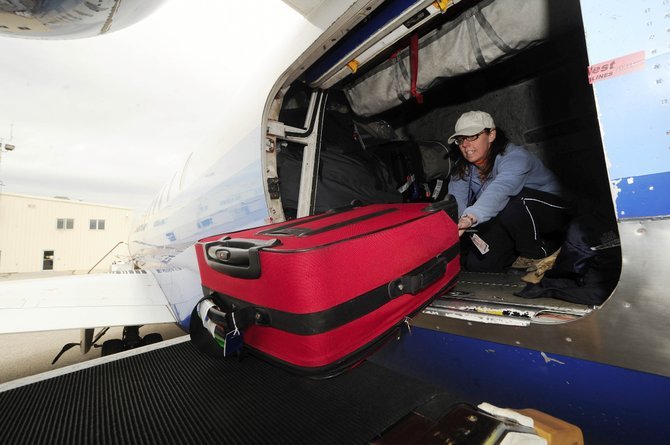 DeAnna Roberts unloads a bag from a United Airlines flight Friday afternoon at Yampa Valley Regional Airport. Officials say they were pleased with the amount of traffic at the airport during the 2008-09 ski season given the state of the economy.