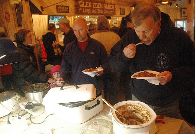 North Routt Fire Protection District firefighter Greg Murray, right, gives some chili a try Sunday at the seventh annual North Routt Chili Cook-off. Murray, attending the event for the fourth year, said it was important for the fire department to be on location to keep a handle on fiery tongues.
