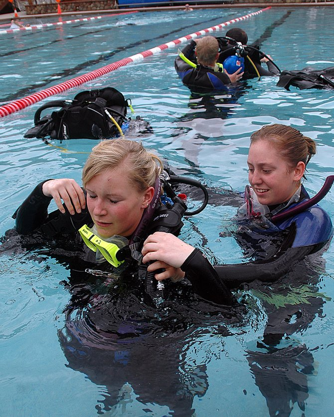 Samantha Huffar helps Cassidy Bush into SCUBA gear Sunday at the Old Town Hot Springs in downtown Steamboat Springs.