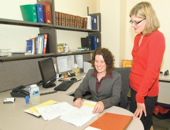 District Attorney Elizabeth Oldham, right, looks over a case with Rebecca Voymas, deputy district attorney, inside the Routt County Justice Center on Monday. The District Attorney's Office is offering to cut back on operational expenses instead of making personnel cuts.