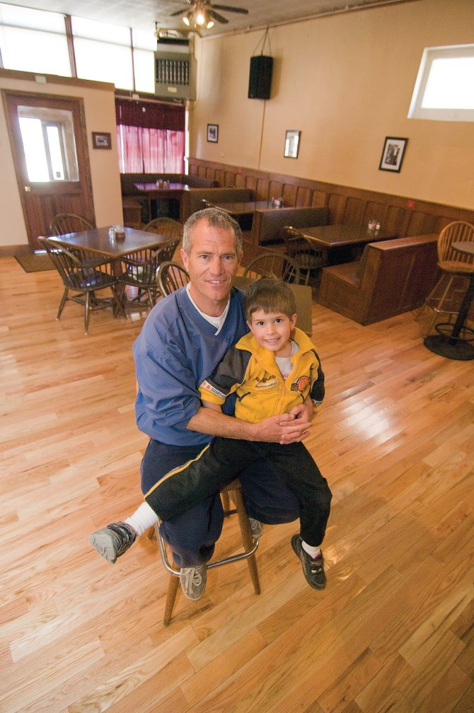 Cody Iacovetto and his son, Isaac, sit inside the new Shorty's Restaurant in Oak Creek. Iacovetto opened the restaurant last week and is offering a variety of items including burgers and steaks.