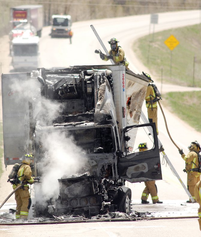 The members of the Steamboat Springs Fire Rescue extinguish a semitrailer blaze at the base of Rabbit Ears Pass on Thursday afternoon. The truck was fully engulfed when the firefighters arrived.