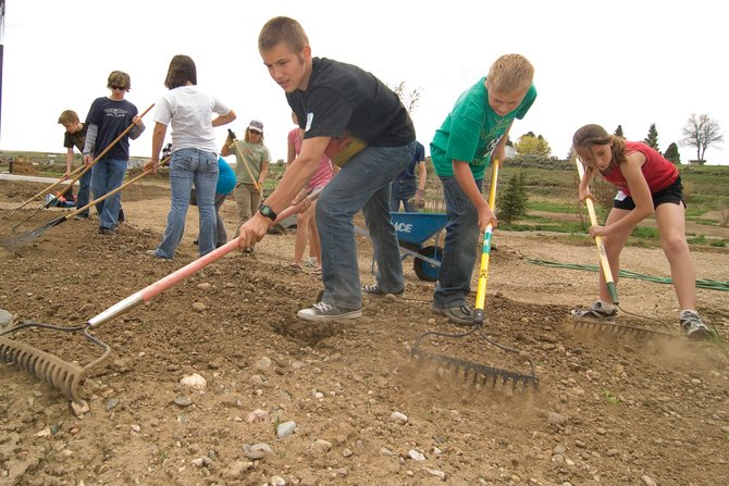 Hayden Middle School students, from left, Nate Mack, Taylor Colding and Neylan Wheat rake the ground at The Haven Assisted Living Center on Tuesday afternoon. The students lent a hand for Global Youth Service Day, organized by school-based mentors for Partners in Routt County.