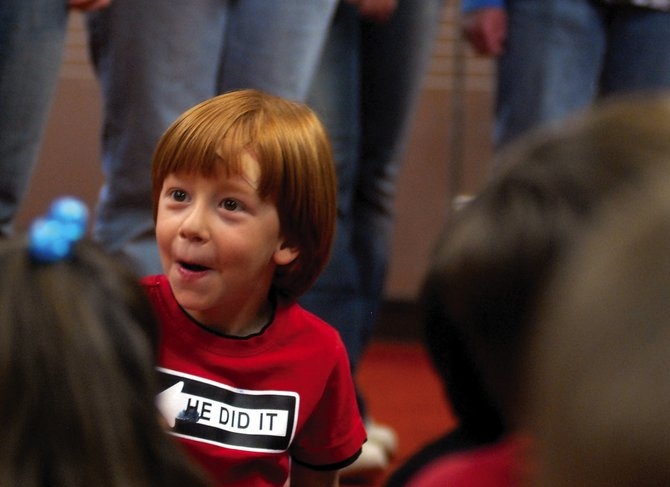 East Elementary School kindergartner Hunter Parfrey reacts to MCHS choir students introducing themselves at the beginning of their visit.