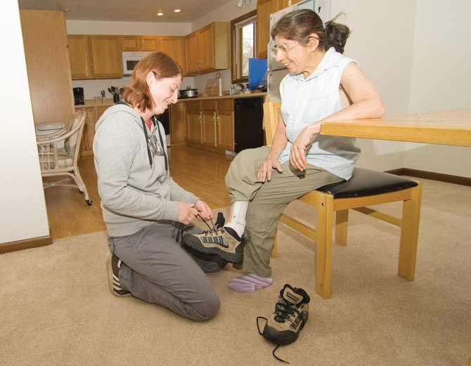 Counselor Courtney Sisson helps client Marcella Chavez with her shoes inside Horizons Specialized Services' new group home in Steamboat II. The home houses three clients and a counselor.