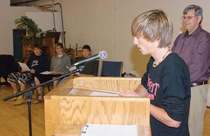 Christian Heritage School graduating senior John Cutter runs through his speech during a practice ceremony while Principal Alan Weisberg observes Thursday morning at the school west of Steamboat Springs. Fellow graduates, from left, Kerry Timmerman, Nicholai Buccino and Jared Finch are seated in the background.