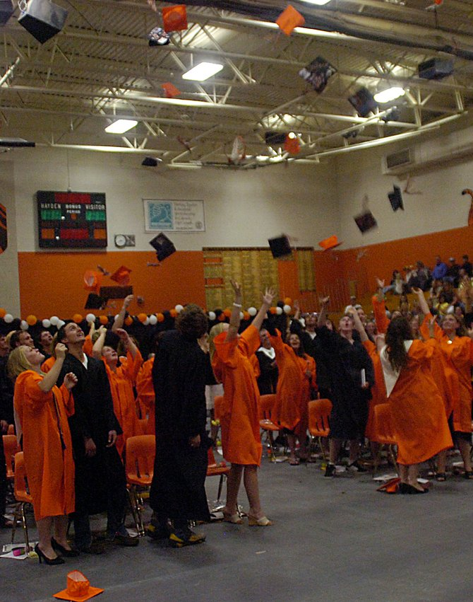 The graduates of Hayden High School celebrate Sunday by tossing their caps into the air at the end of the school's 100th graduation ceremony.