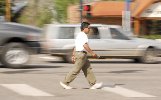 Abal Aquino walks along Lincoln Avenue as Monday afternoon traffic rushes by him. City Council members will discuss the best options for dealing with the Colorado Department of Transportation's pavement replacement project on Lincoln Avenue through downtown this summer. The project will begin after Labor Day this year and will conclude in 2010 and is expected to affect motorists and pedestrians.