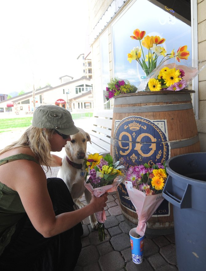 "Slopeside Grill bartender Rebecca Boucha places a bouquet of flowers in front of the restaurant Tuesday afternoon in memory of her boss Chris Corna. ""He was a good friend and an even better boss,"" Boucha said."