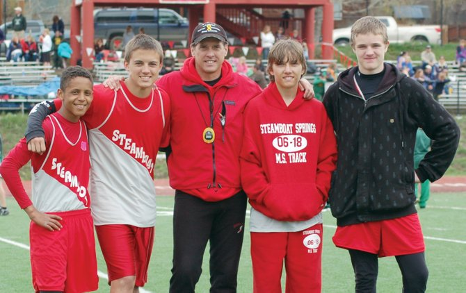 Keenan Bradshaw, from left, Michael Yost, coach Scott Lewer, Colton Lewer and Dylan Wilkinson take a break at the Steamboat Springs Invitational, which was held May 2 in Steamboat Springs. The athletes were part of Steamboat&#39;s 800-meter relay team, which won the event at the middle school track meet.