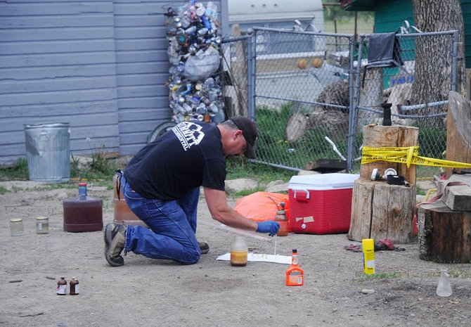 A worker with Summitt Environmental, who refused to give his name, examines chemicals Friday that were found Thursday night at a home east of Hayden. Six marijuana plants also were seized from the home.