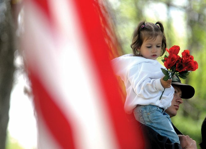 Mara Beckett, 3, sits on the shoulders of her father, Martin Beckett, on Monday during the Memorial Day service at Craig Cemetery. Mara is holding a bouquet for her grandfather, Delf A. Martinez, and great-grandfather, Eliseo Martinez, both Army veterans, who are buried at the cemetery. The Veterans of Foreign Wars Post 4265, American Legion Post 62 and the Sons of the American Legion hosted the service, which was open to anyone wishing to pay their respects to veterans.