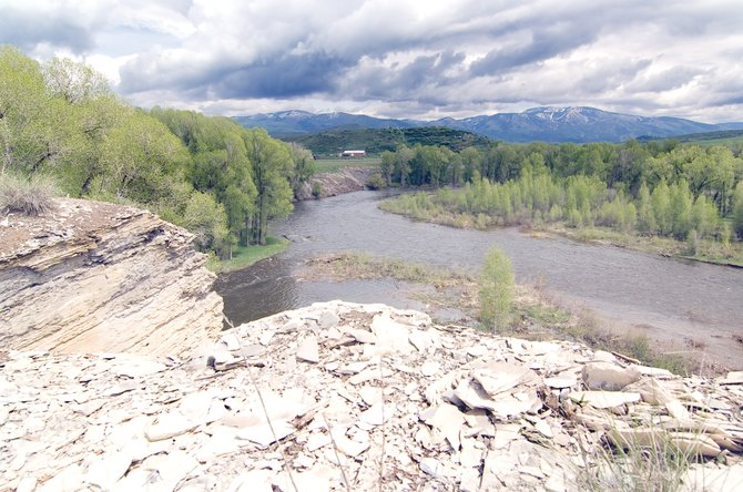 The Yampa River pushes its banks west of Steamboat Springs as afternoon thunderclouds build over the slopes of Steamboat Ski Area. Despite recent rain, the Yampa and Elk rivers have peaked, and levels are trending downward, according to the National Weather Service.