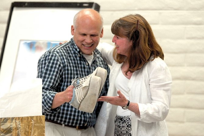 "Pete Bergmann, Moffat County School District superintendent, receives a gift from Janele Husband on Tuesday night during an open house at the American Legion Post 62 in his honor. Bergmann is retiring, and his last day is June 30. Husband gave him a pair of sneakers to help him ""walk into retirement."""