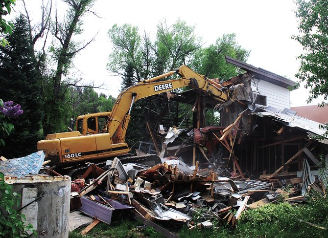 A track hoe razes a house at 655  Yampa St. on Monday. It was one of the last four single-family homes on the street paralleling the Yampa River.