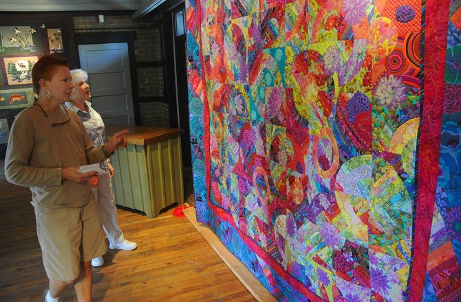 Quilter Jackie Grimaldi, left, talks to Steamboat visitor Mickey Bement about a quilt Grimaldi has hanging at the Depot Art Center. An exhibit for the Delectable Mountain Quilt Guild will open Friday with a reception at 5 p.m.