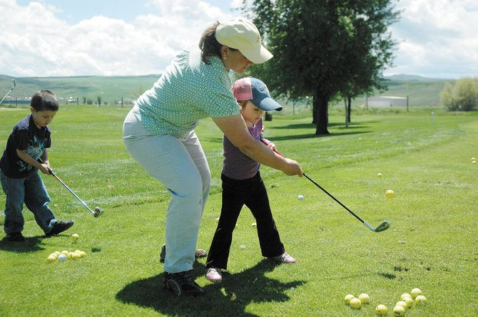 Ann Marie Roberts, middle, assists AnnMarie Counts, 4, with her swing. For the fifth straight year, Roberts and Brett Etzler have taught 4- to 12-year-old children the fundamentals of golf.