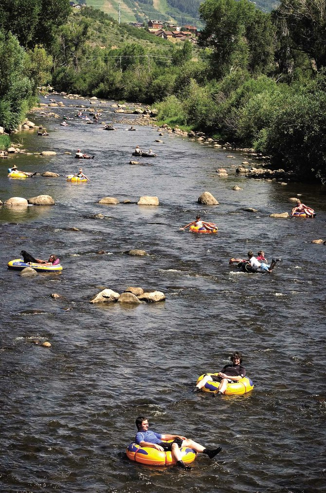 Tubers dot the Yampa River through downtown Steamboat Springs on a Saturday afternoon in July 2007. As tubing season nears in 2009, members of the Respect the Yampa campaign are reminding river users to reduce their impact on wildlife habitat on the river.