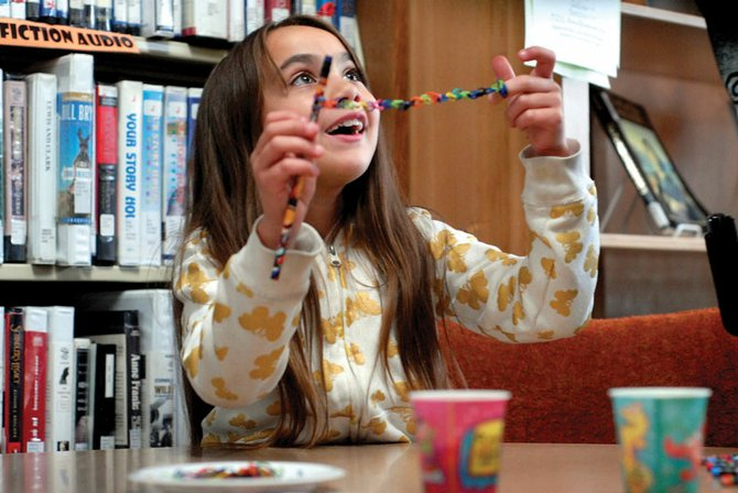 Desiree Solano, 8, finishes a rubber-band bracelet she made Wednesday as part of the Moffat County Libraries' Express Yourself Youth Club, a part of the Summer Reading Program. The program also includes a story-time for all ages Thursdays at Moffat County Fairgrounds picnic area.