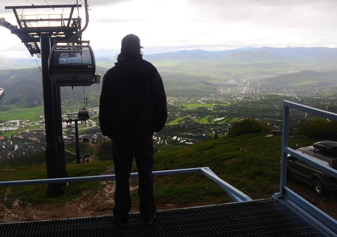Steamboat Ski and Resort Corp. lift supervisor Brian Crosby looks across the Yampa Valley on Wednesday as an afternoon storm moves out of the area. Crosby, along with other members of the gondola's Silver Bullet Maintenance crew, had to wait for the storm to pass before removing the rest of the cars from the line.