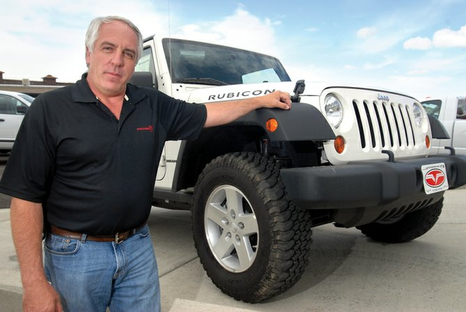 Chris Maneotis, co-owner of Victory Motors of Craig, stands next to a new Jeep Wrangler, delivered to his lot Thursday. Victory acquired the Jeep brand after Chrysler took it away from Cook Chevrolet earlier this week.