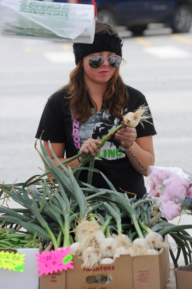 Sweet Pea Market employee Jules Poma shucks fresh garlic Saturday at the Mainstreet Farmers Market. Sweet Pea owners Jonathon Hieb and Katherine Zambrana want to open a stand near Ace at the Curve.