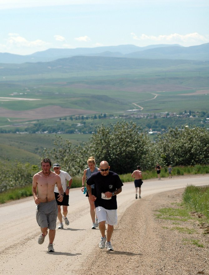 Daniel Renner, left, and Kyle Johnson, lead a pack of runners up Cog Road on Saturday during the 31st annual Hayden Cog Run. The event was coupled with Huck Finn Day at the Hayden City Park and also featured 5- and 10-kilometer runs. Turnout this year was nearly three times that of last year.