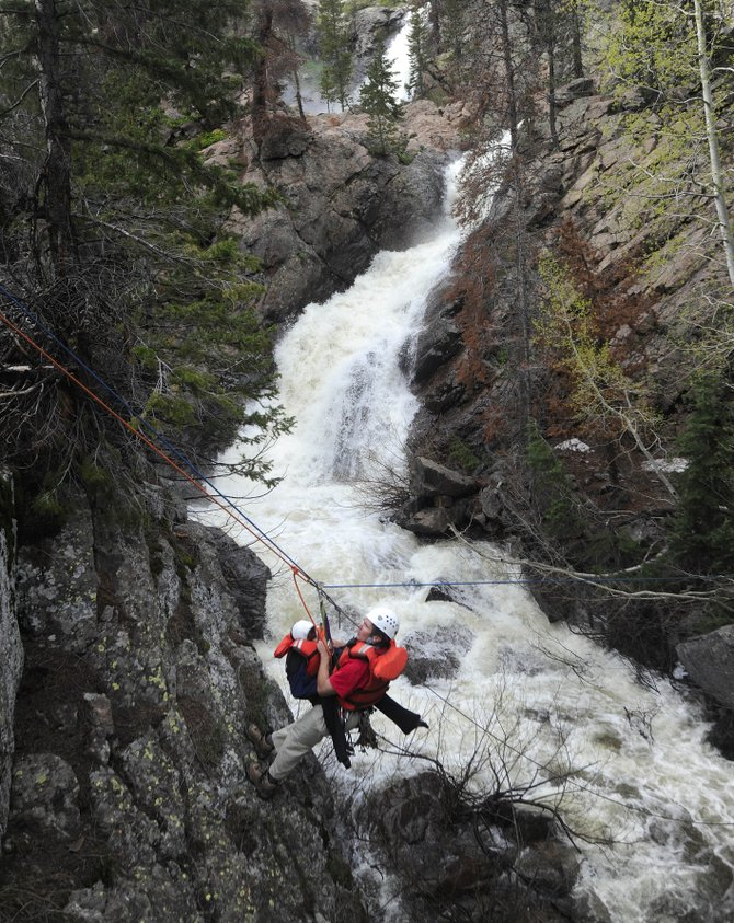 Routt County Search and Rescue President Russ Sanford takes Kade Green, then 8, across Fish Creek on June 13, 2009 in a rescue mission. Search and Rescue is in the midst of its annual effort to recruit new volunteers.