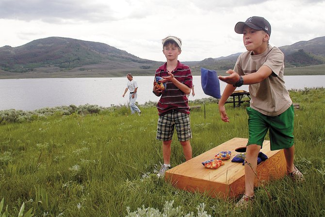 Lowen Epstein, left, and Everett Simonsen toss beanbags Sunday near the shores of Stagecoach Reservoir. Historic Routt County staged an event at the lake that featured games, food and an auction to help raise money to preserve the Diamond Window Cabin near the reservoir.