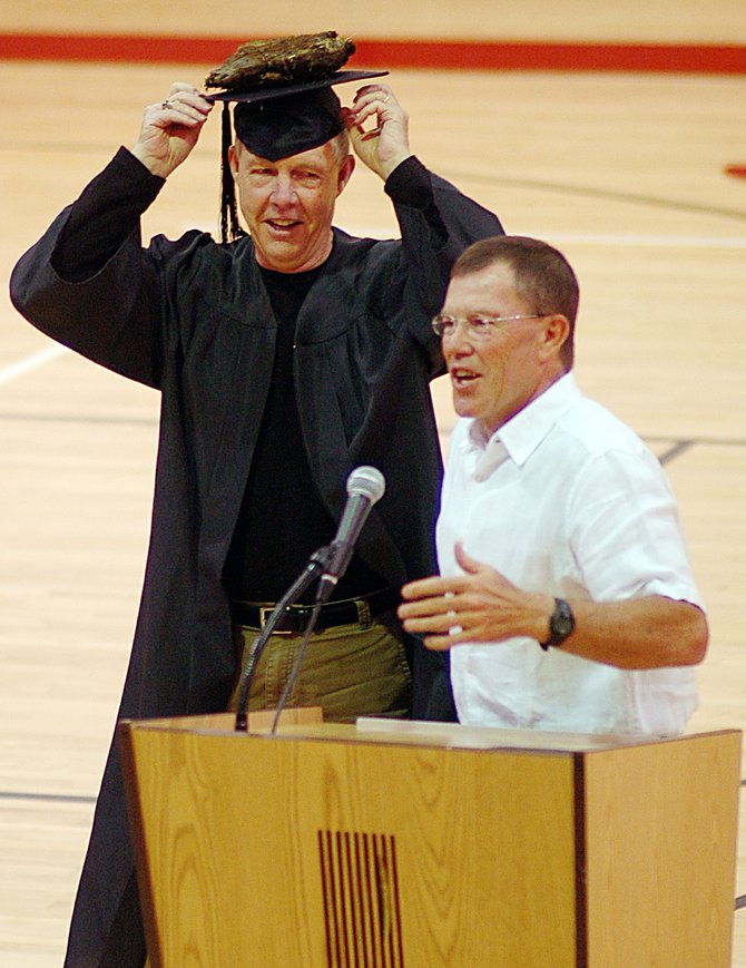 "Kelly Meek adjusts his cap after Moffat County basketball coach Craig Mortensen ""awarded"" him a doctorate in B.S. on Saturday as Meek was roasted at Steamboat Springs High School."