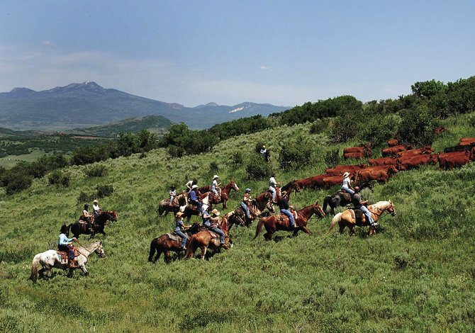 Cowpokes and guests at Marabou Ranch move a small herd of cattle to a fresh pasture in June 2007 with Sand Mountain in the background. The views from the summit of Sand Mountain allow hikers to stand in one spot and gaze into downtown Craig and Steamboat.