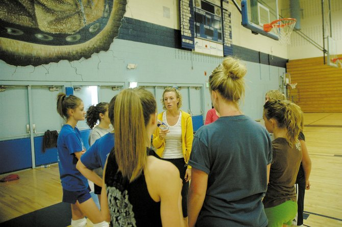 Coach Brianna Montgomery, center, talks to her Moffat County High School volleyball team during practice Wednesday at the school. Montgomery, who is entering her fourth year as head coach, said she will have a young team this year.