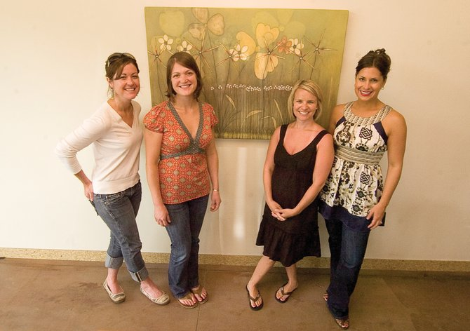Katy Vaughn, from left, Maureen McQuillin, Shelly Bisbee and Kimberly Saari stand in front of the mixed media that will be used for the cover of the Yampa Valley Arts & Gallery Guide, which comes out Friday.