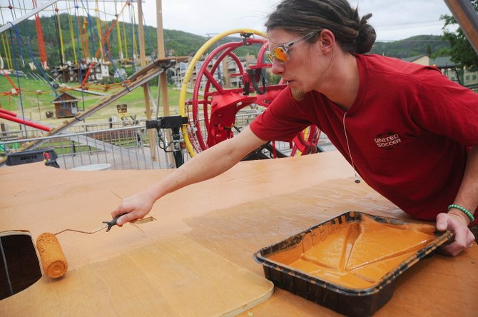 Eric Boppel, of Steamboat Springs, puts a coat of paint on the trampoline deck being constructed in the Coca Cola Adventure Zone. The activity area opens Saturday with the free Family Fun Fest from 10 a.m. to 2 p.m.