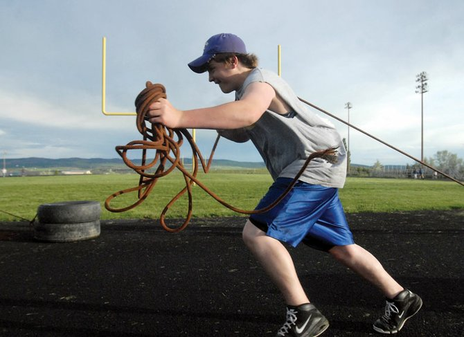 Sophomore Mason Updike drags tires Thursday during Moffat County High School football summer workouts. The camp uses old-school techniques for training.