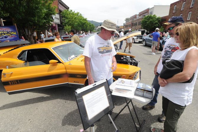 Denver resident Wes Young, left, talks to Walden residents Colleen Conroy and Bill Boatman about Young's refurbishing of a 1970 Mach 1 Twister Special Mustang. Young brought his car to Steamboat Springs for the Rocky Mountain Mustang Roundup Show n' Shine on Saturday on Lincoln Avenue.