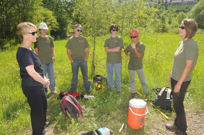 Lt. Gov. Barbara O'Brien, left, talks to Steamboat Springs Community Youth Corps crew leader Jess Schnittka, right, along with 14-year-old Youth Corps crew members, from right, Max May, Andrew Watterson, Jack Triolo and Kent Barron on Tuesday on Snake Island in the Yampa River.