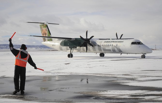 Yampa Valley Regional Airport ramp agent Kirklann Baker waves in a Frontier Airlines plane in December 2008. The airline has announced it will not return to YVRA during the 2009-10 ski season, but officials did not rule out a return in future winters.