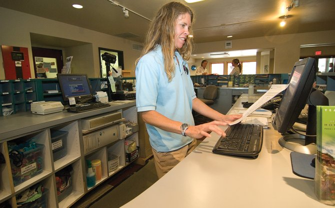 Old Town Hot Springs employee Krista Drobek works the front desk at the downtown business. Old Town Hot Springs is part of the Steamboat Springs Chamber Resort Association's Spurs on Service hospitality program.