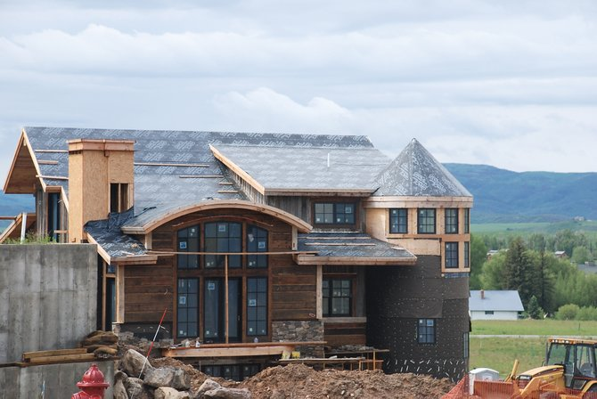 The home under construction in The Range at Wildhorse Meadows is among a few luxury homes being built in Steamboat this summer. Gary and Teri Wall, founders of a local Home Builders Association chapter, say the group will help people in the industry work together. 