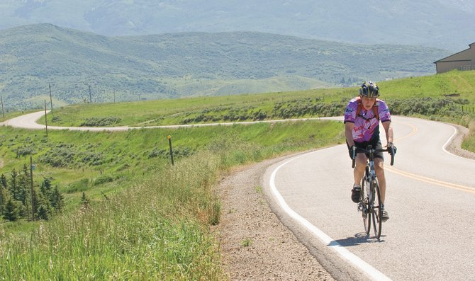 Cyclist Sam Zimmerman rides along Routt County Road 33 on Monday morning just outside of Steamboat Springs.