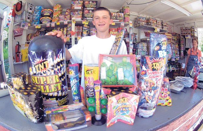 Sale's clerk Charles Toye, one of several employees who work for Mary Dike (background) at the TNT Fireworks stand on the west side of downtown Steamboat Springs, sits in front of a large assortment of fireworks that are legal in Routt County. Toye and Dike stressed that legal fireworks still need to be used responsibly.
