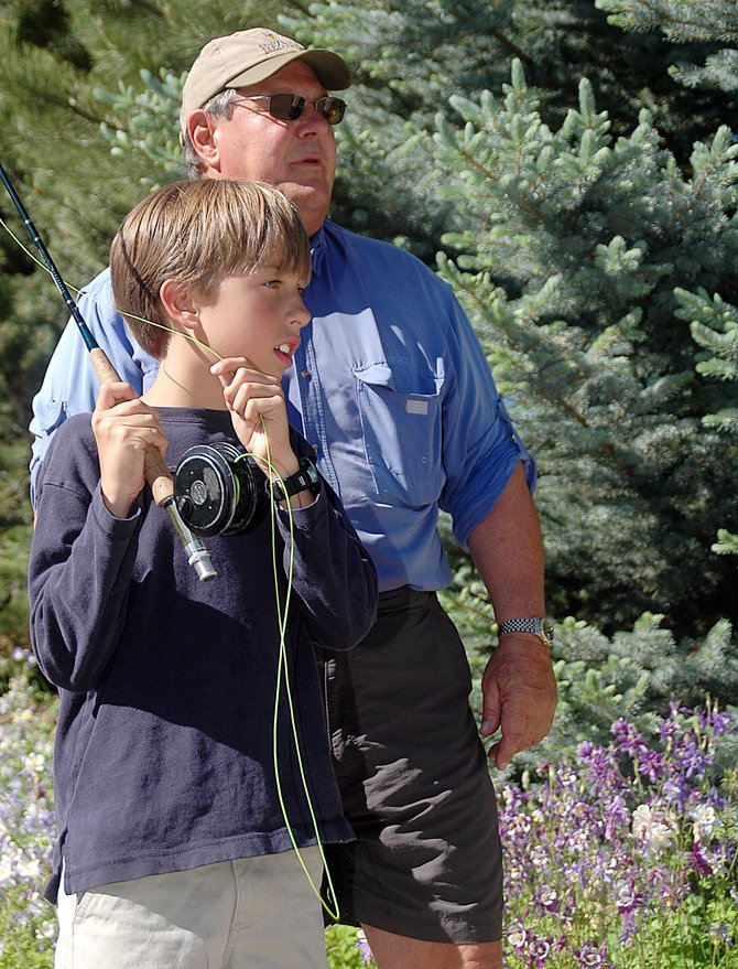 Jim Zaccone, of the Yampa Valley Stream Improvement Chartable Trust, helps Hunter Esswein, 8, learn to cast Sunday during the Yampa Valley Community Foundation's 30th anniversary celebration at Yampa River Botanic Park. During the event, the Community Foundation announced a Community Cares Fund initiative that aims to raise $30,000 in 30 days to distribute to residents who need basic living assistance as a result of the economic recession.