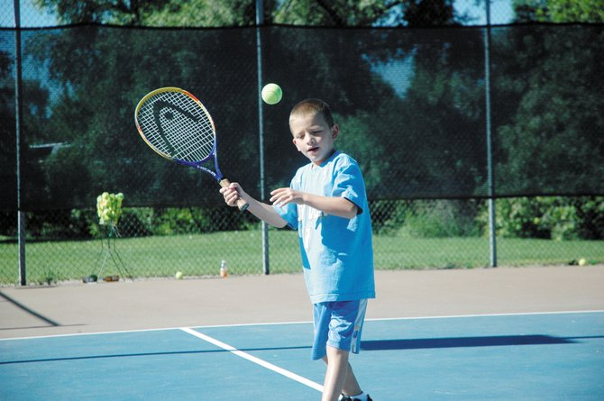 Kai Bertram, 7, gets ready to serve the ball Tuesday at the tennis courts at Victory Way and Lincoln Street. The Boys & Girls Club of Craig brings youths to the courts once a week.