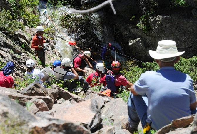 Rebecca Green's father, Eldon Adams, right, watches rescuers Tuesday morning as they work to recover the body of Green in Fish Creek below the second falls.